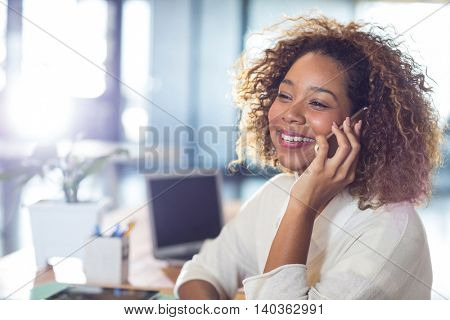 Happy woman talking on mobile phone in office