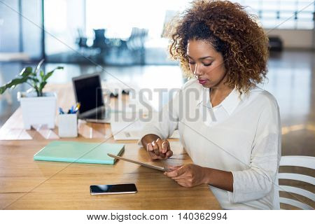 Woman using digital tablet at table in office