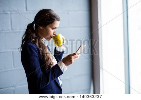 Woman drinking coffee while using mobile phone in office