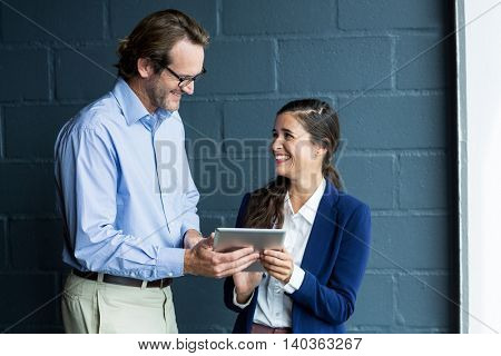 Happy man and woman using digital tablet against wall in office