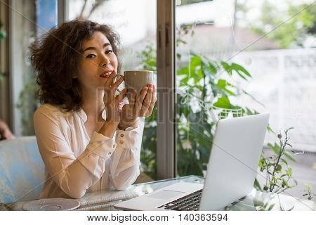 Asian girl with a cup of tea and a laptop sitting in a cafe.