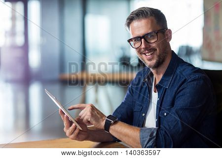 Portrait of smiling man using digital tablet in creative office