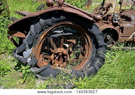 Rotten flat tire on a very old rusty tractor with a crumpled fender