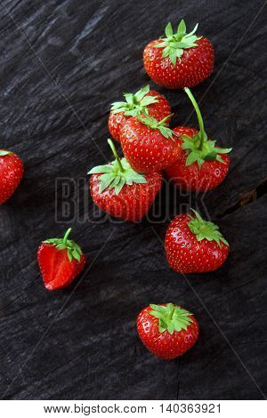 Red fresh strawberries on black rustic wood background. Scattered three natural ripe organic berries with peduncles on wooden surface, top view, vertical image