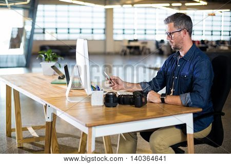 Man using mobile phone at table in office