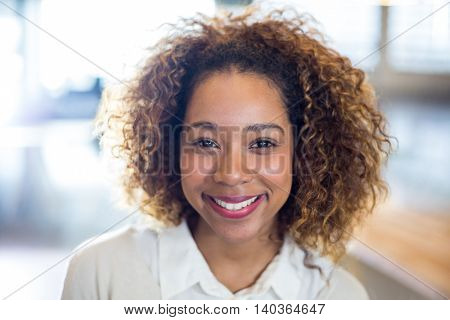 Portrait of smiling woman with curly hair in office