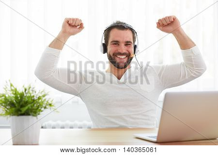 Happy Male Operator With Headset And Notebook In The Office
