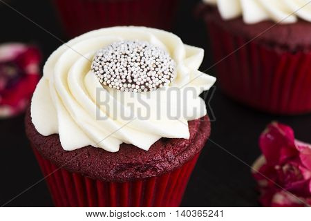 Red velvet cupcakes and roses buds over grunge wooden background. Selective focus