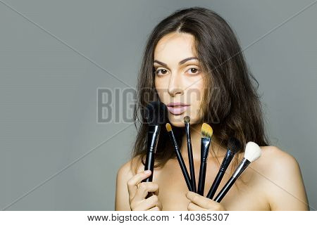 young woman with pretty face and long brunette hair with sexy bare shoulders of female body holding fashionable makeup brush set in studio on grey background copy space