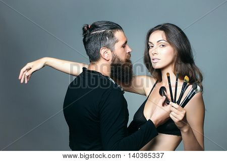 young couple of sexy woman with pretty face and long brunette hair in black bra on body and handsome bearded man visagiste with fashionable makeup brush in studio on grey background