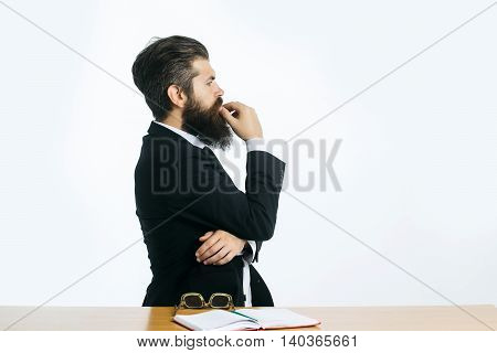 young handsome bearded man scientist or professor with long beard and teacher glasses with book or notepaper sitting at table isolated on white background