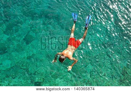 Man snorkeling in a tropical sea in Thailand