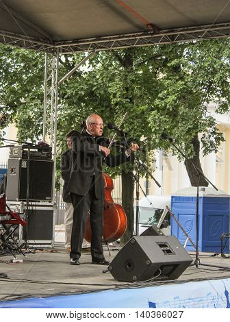 St. Petersburg, Russia - 23 July, Musician with a violin at the microphone, 23 July, 2016. Speech by David Goloschekin with his jazz group on the Arts Square in St. Petersburg.