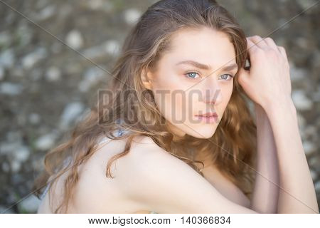 Pretty girl young woman with natural blond curly long hair and beautiful face poses outdoor on summer day
