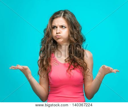The portrait of disgusted woman on blue background. the concept of heavy choice