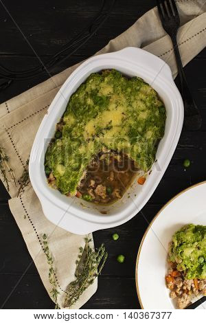 Comfy food - casserole with ground meat, vegetables, pea puree and parmesan. Top view. Selective focus