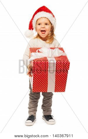 Laughing 3 years old little girl carrying big red polka dot gift box with white ribbon