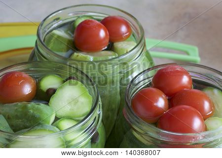 Pickling cucumbers and tomatoes. Cucumbers tomatoes and spices packed in glass jars. Flooded with marinade. Stocking up for winter.