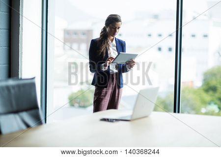 Focused young woman using digital tablet in creative office