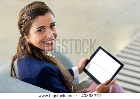 Portrait of happy woman holding digital tablet while sitting on sofa in office