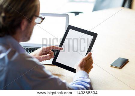 Businessman using digital tablet in creative office