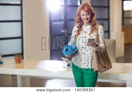 Smiling young woman using mobile phone while holding mat in creative office