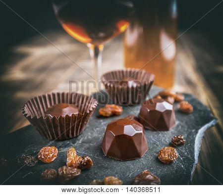 Chocolate praline with raisin on black background