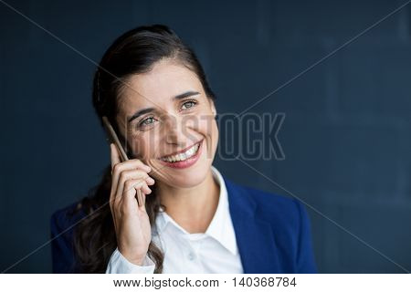 Smiling young woman talking on phone in office