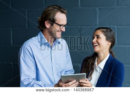 Smiling colleagues discussing while holding digital tablet against wall in office