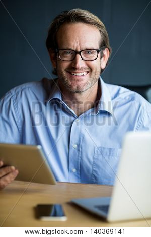 Portrait of smiling man using laptop in creative office