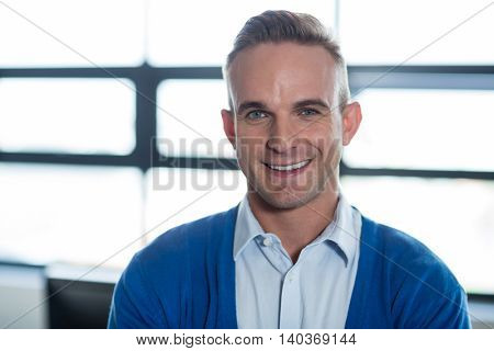 Portrait of smiling young man standing in office