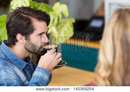 Man sitting at counter drinking cup of coffee in cafe