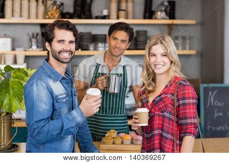 Portrait of smiling couple standing at counter holding cup of coffee in cafe