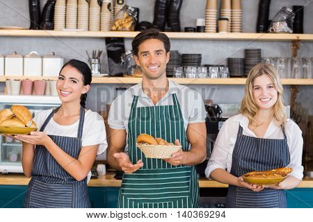 Portrait of smiling waiter and two waitresses holding plate of bread rolls at cafe
