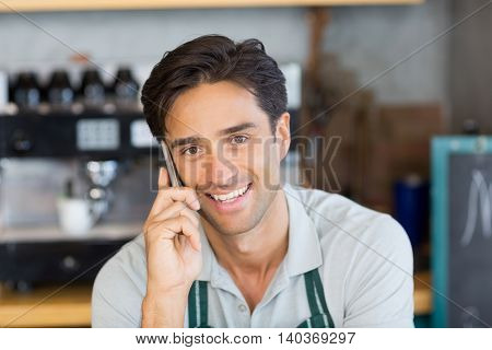 Portrait of waiter talking on mobile phone at cafe