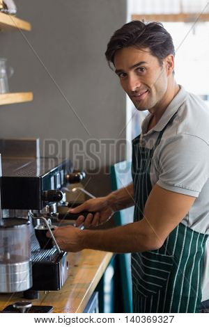 Portrait of smiling waiter making cup of coffee at cafe