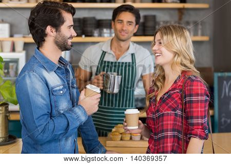 Happy couple standing at counter holding cup of coffee in cafe