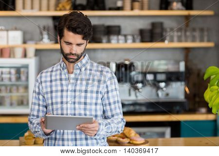 Man standing at cafe using digital tablet