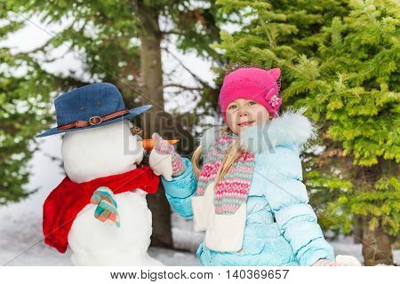 Little blond girl put carrot nose to snowman in the winter forest