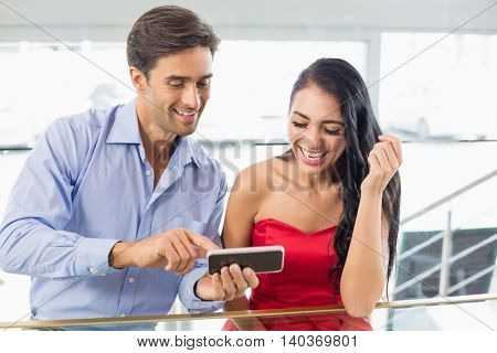 Happy couple sitting in cafe using mobile phone
