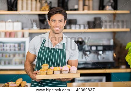 Portrait of smiling waiter holding a tray of cupcakes at cafe