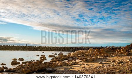 Fisherman standing at the rocky beach South Australian shore