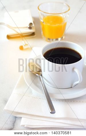 Morning coffee orange juice and mobile phone on the marble table