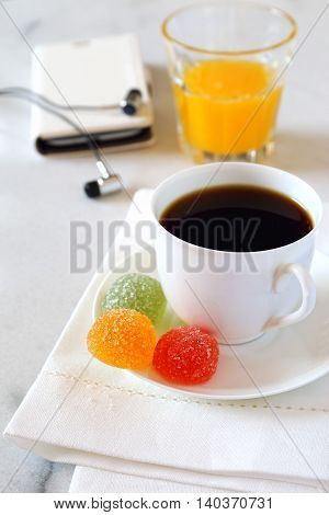 Morning coffee orange juice gummi candy and mobile phone on the marble table
