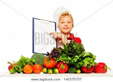 Kid boy in cook's uniform holding blanked clipboard menu, standing behind the table full of fresh vegetables, isolated on white