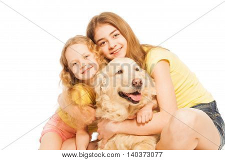 Portrait of two age-diverse sisters, beautiful blond girls, hugging their Golden Retriever doggy, isolated on white