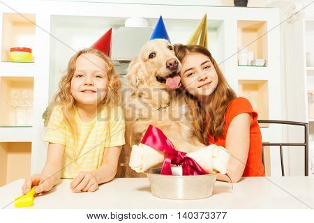 Two smiling girls in party hats celebrating  Birthday of their Golden Retriever doggy, sitting at the festive table
