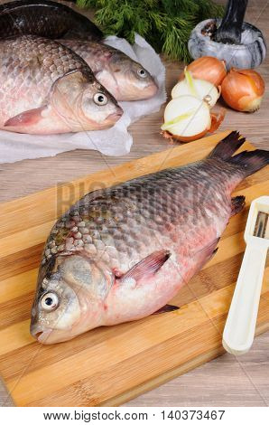 Fresh crucian carp lying on a cutting board for cutting cooked