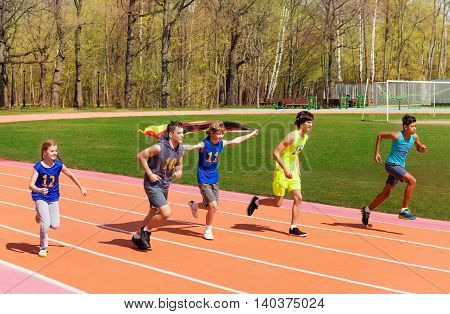 Group of five teenage sprinters running on the track with German flag