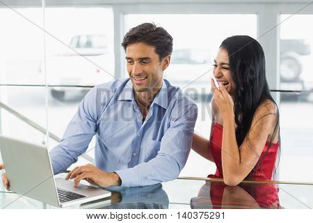 Happy couple sitting in cafe using laptop